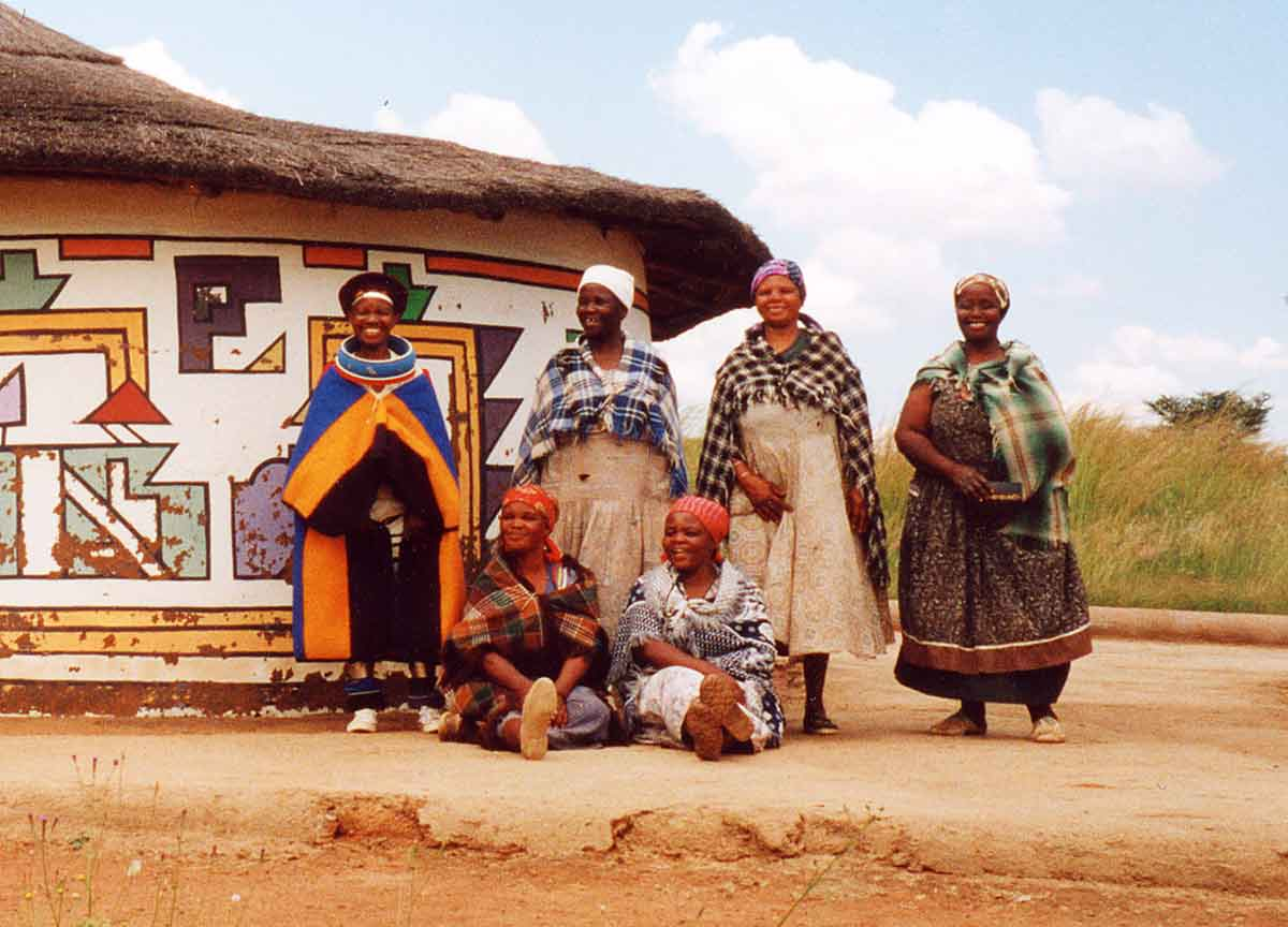 Ndebele women in front of a patterned house