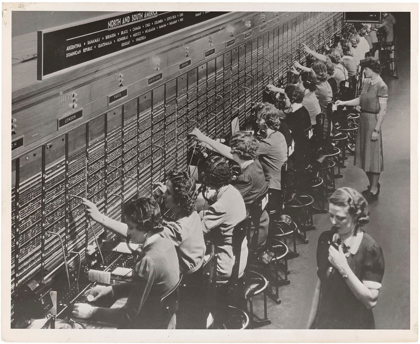 A black and white photograph showing a row of women sitting in front of big switchboards