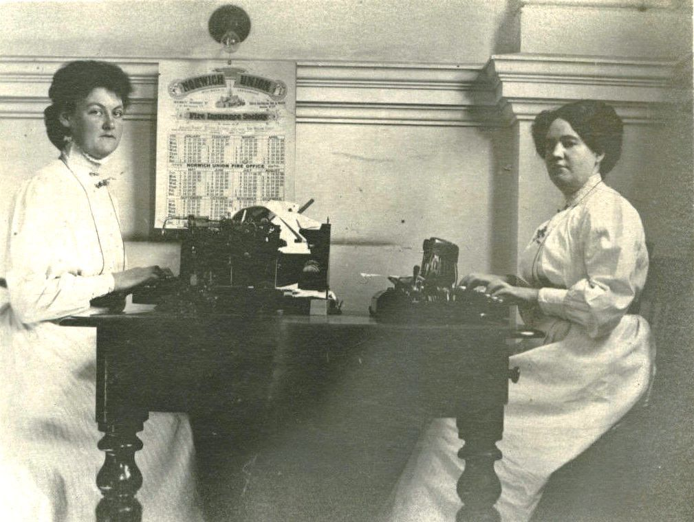 A black and white photograph of two women sitting across each other on a table, their hands lying on typewriters in front of them